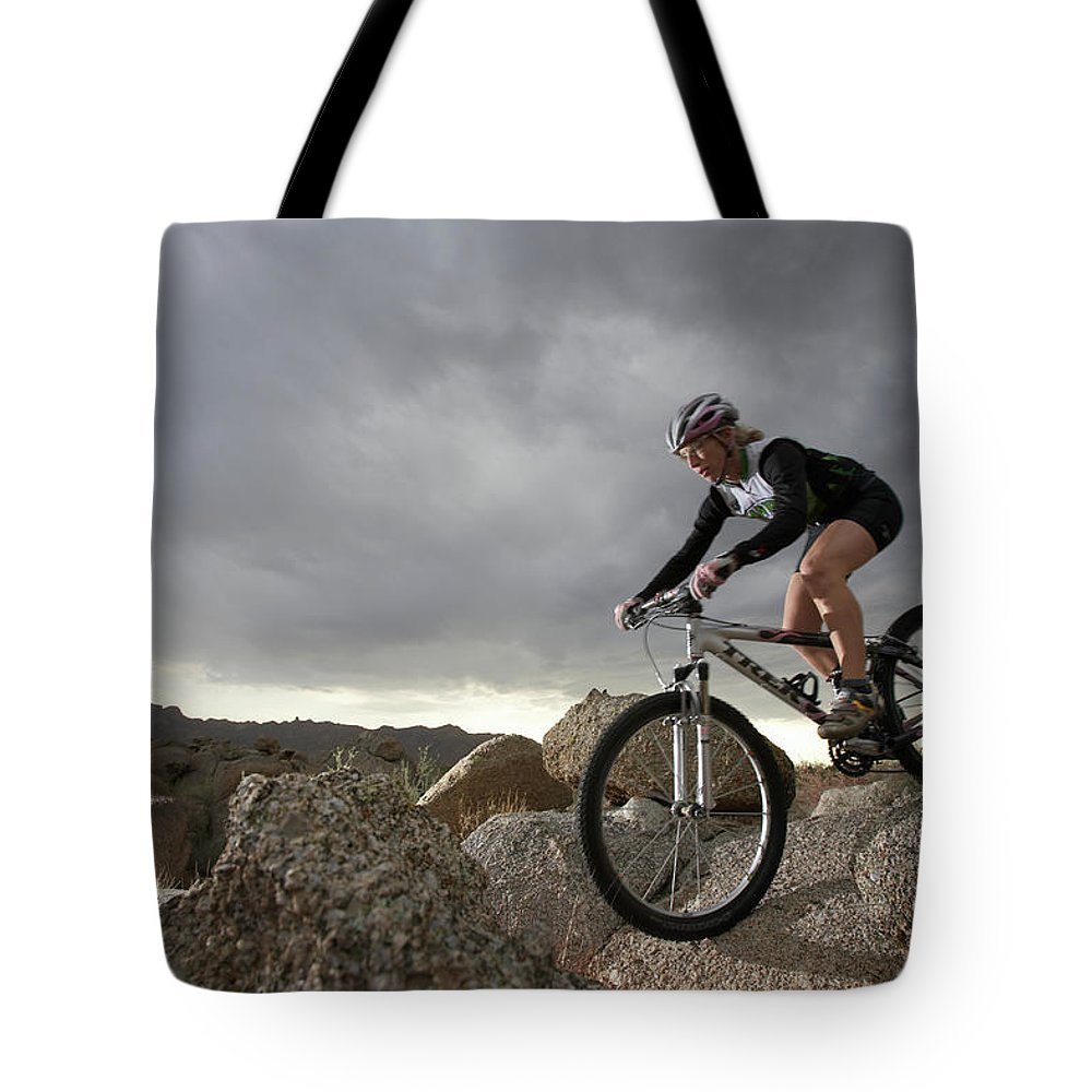 Sports Helmet Tote Bag featuring the photograph Female Rider Mountain Biking Between by Thomas Northcut