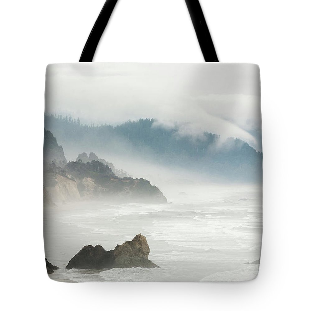 Scenics Tote Bag featuring the photograph Fog Shrouded View Of Rocky Coastline by Win-initiative