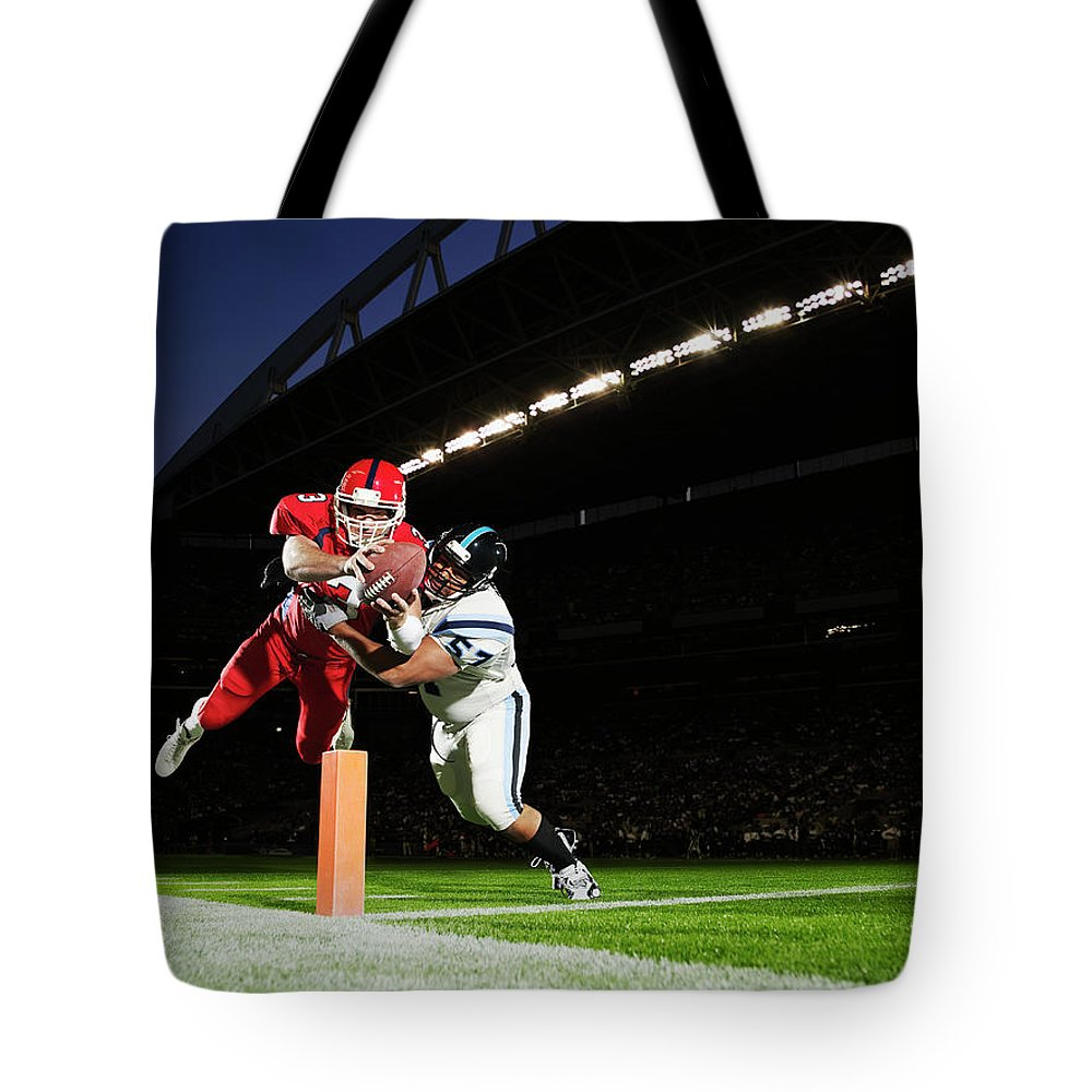 Sports Helmet Tote Bag featuring the photograph Football Player Diving Into End Zone by Thomas Barwick
