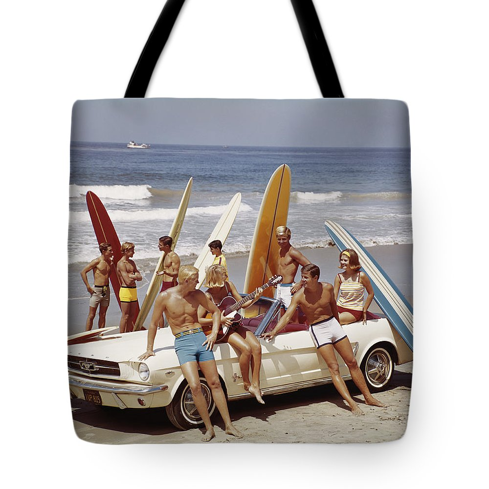 Young Men Tote Bag featuring the photograph Friends Having Fun On Beach by Tom Kelley Archive