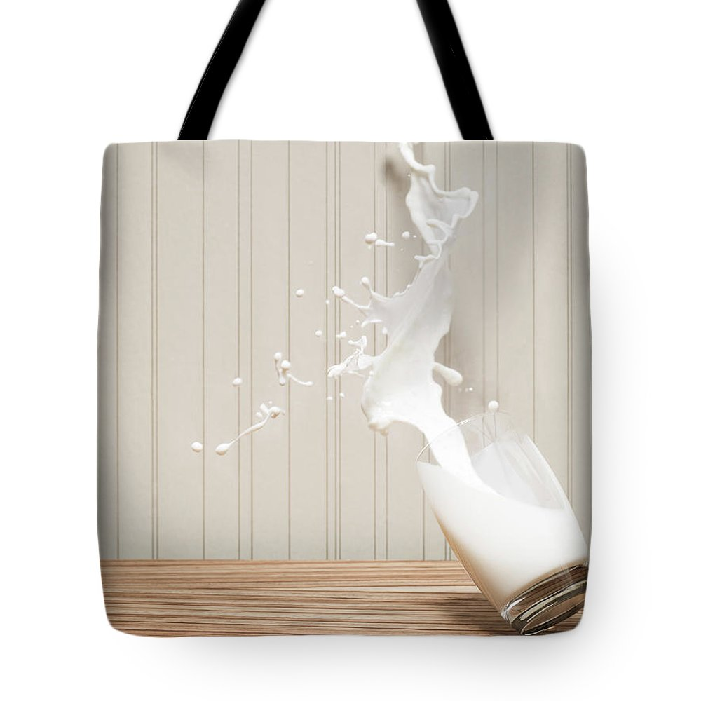Milk Tote Bag featuring the photograph Glas Of Milk Spilling by Henrik Sorensen