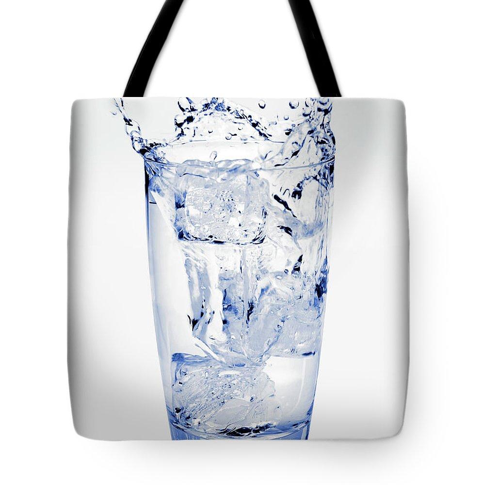 White Background Tote Bag featuring the photograph Glass Of Water Splashing Around by Maria Toutoudaki