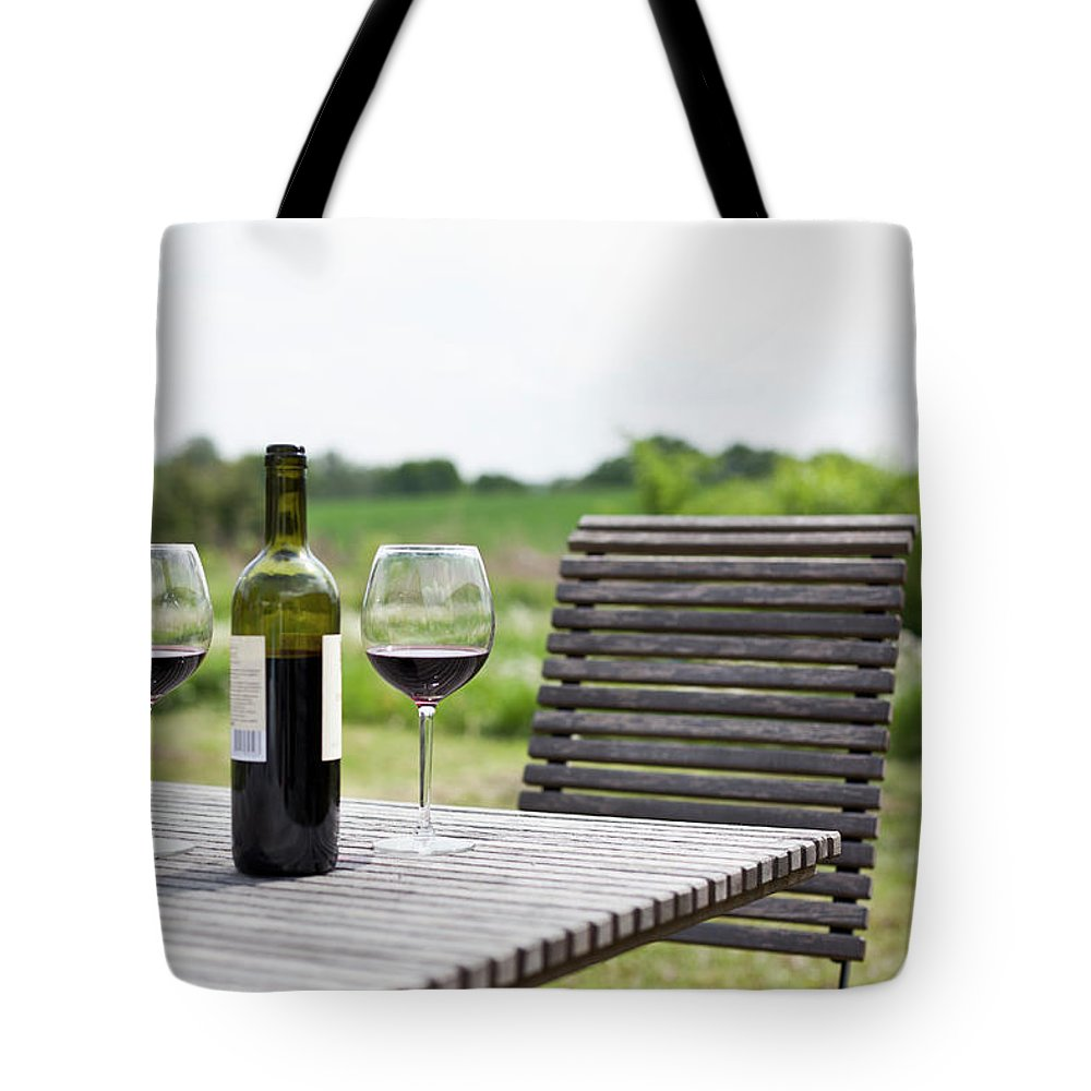 Five Objects Tote Bag featuring the photograph Glasses And A Bottle Of Red Wine On An by Halfdark