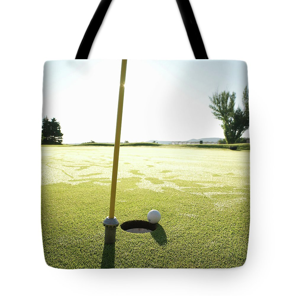 Grass Tote Bag featuring the photograph Golf Ball Near Hole At Sunrise, High by Ascent/pks Media Inc.