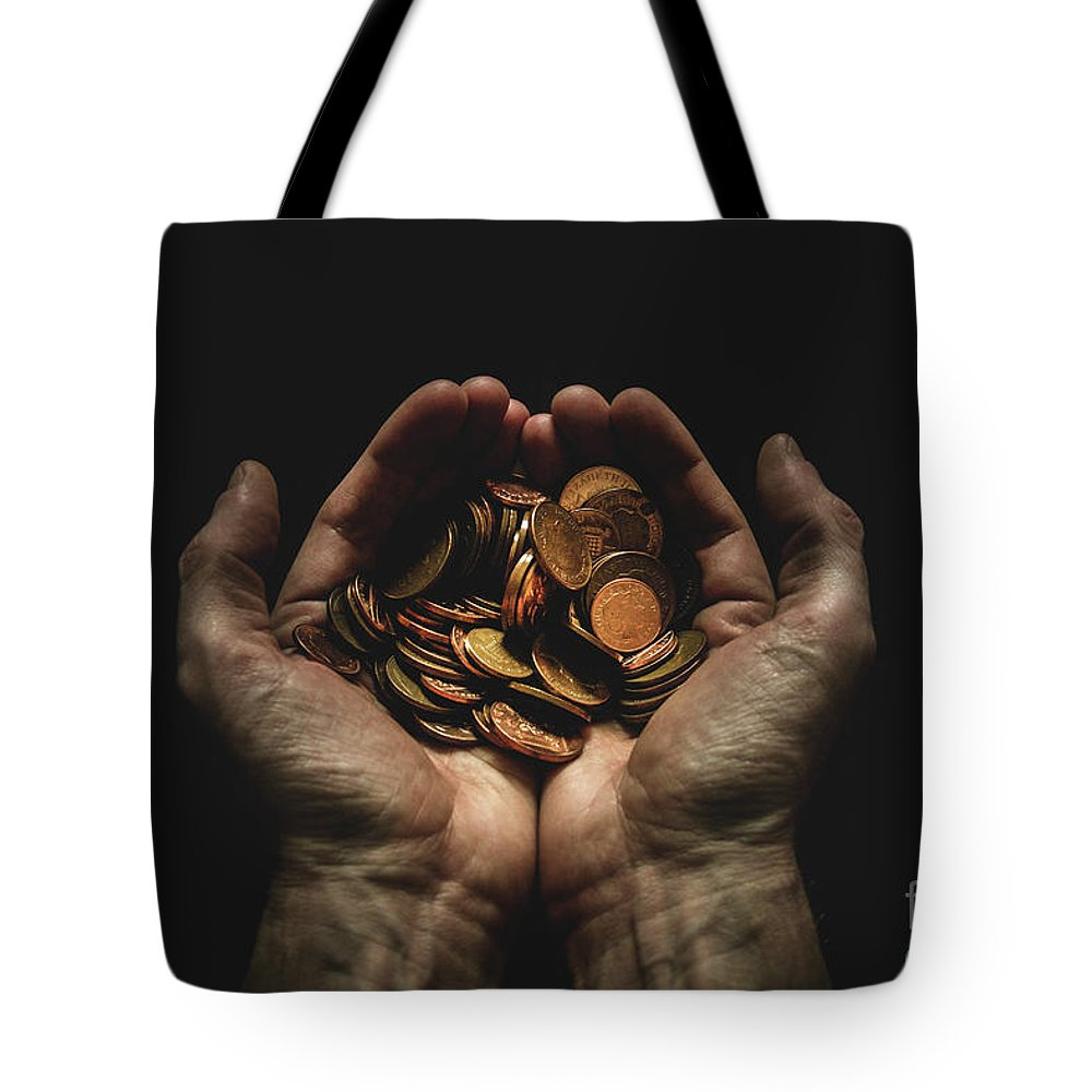 Coin Tote Bag featuring the photograph Hands Holding Coins Against Black by Andy Kirby