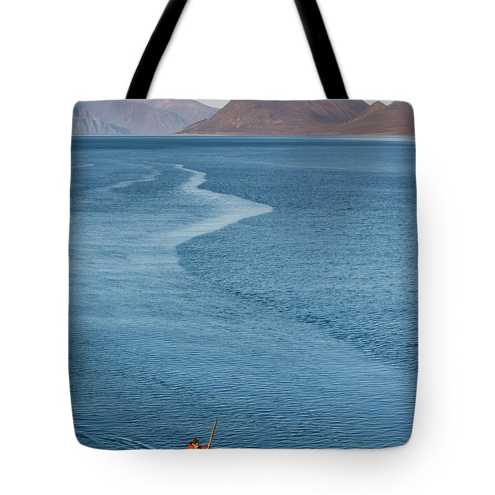 People Tote Bag featuring the photograph Inuit Man Paddling Traditionally Shaped by Andrew Peacock