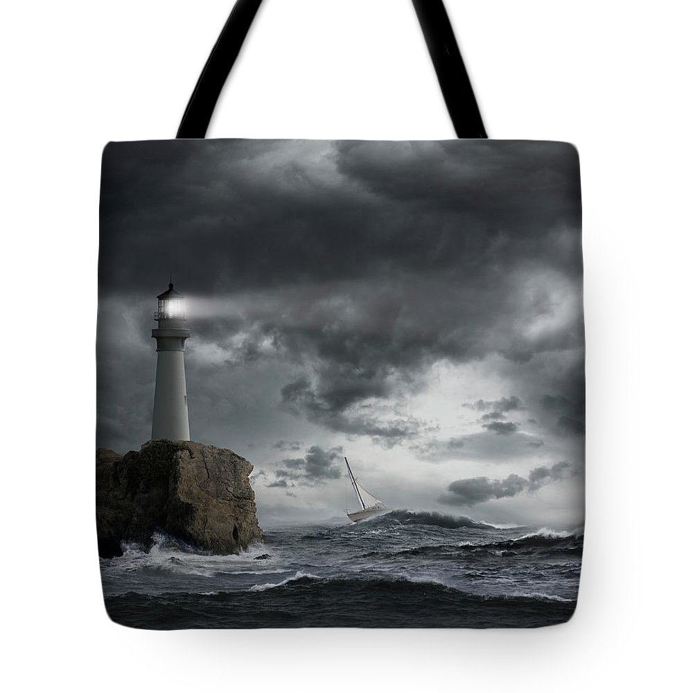 Risk Tote Bag featuring the photograph Lighthouse Shining Over Stormy Ocean by John M Lund Photography Inc