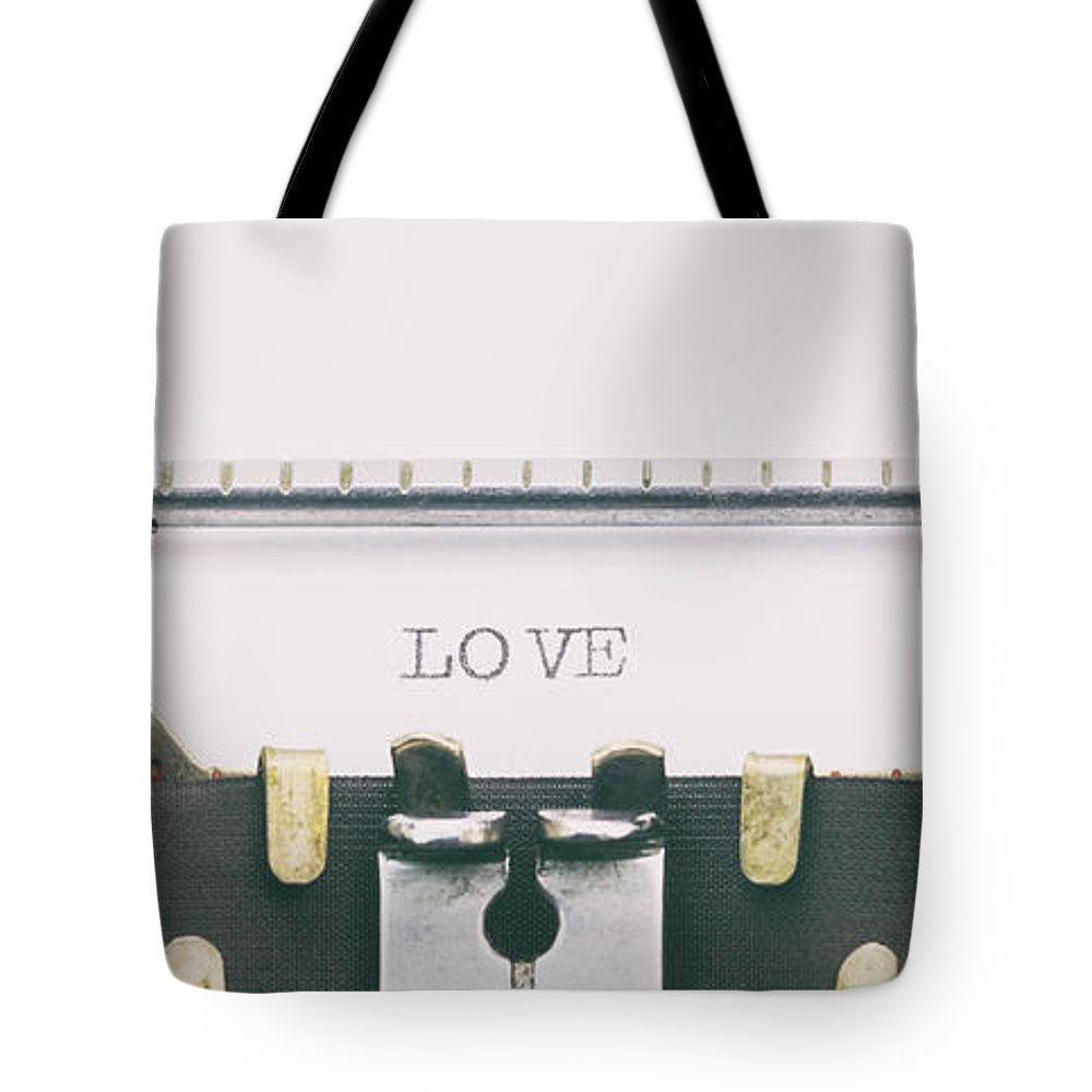 Typewriter Tote Bag featuring the photograph Love Word In Capital Letters On A Typewriter Sheet by George Tsartsianidis