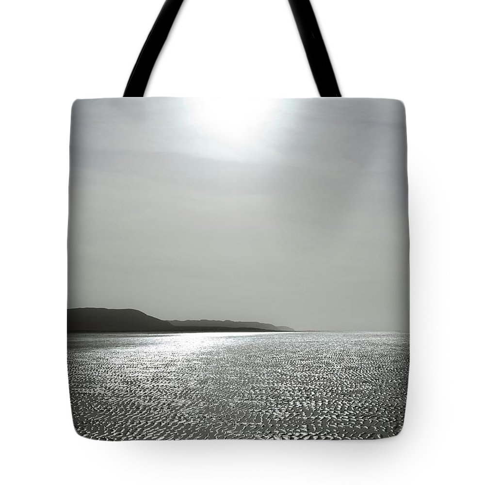 Silver Tote Bag featuring the photograph Low Tide Sandy Beach Ripples Silhouetted Against Sun by Unknown
