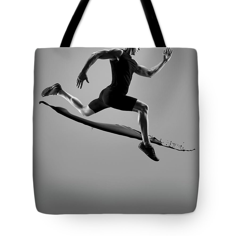 People Tote Bag featuring the photograph Male Athlete Running Above Liquid Splash by Jonathan Knowles