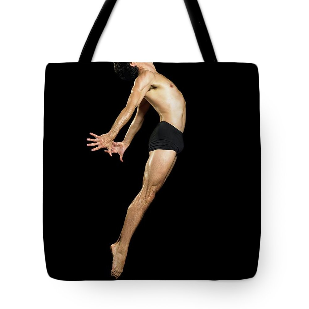 Human Arm Tote Bag featuring the photograph Male Dancer Jumping by Image Source