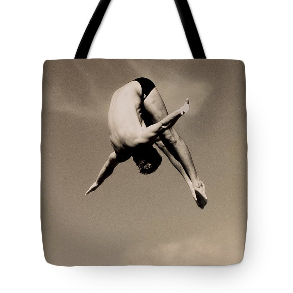 Diving Into Water Tote Bag featuring the photograph Male Diver In Mid-air by David Madison