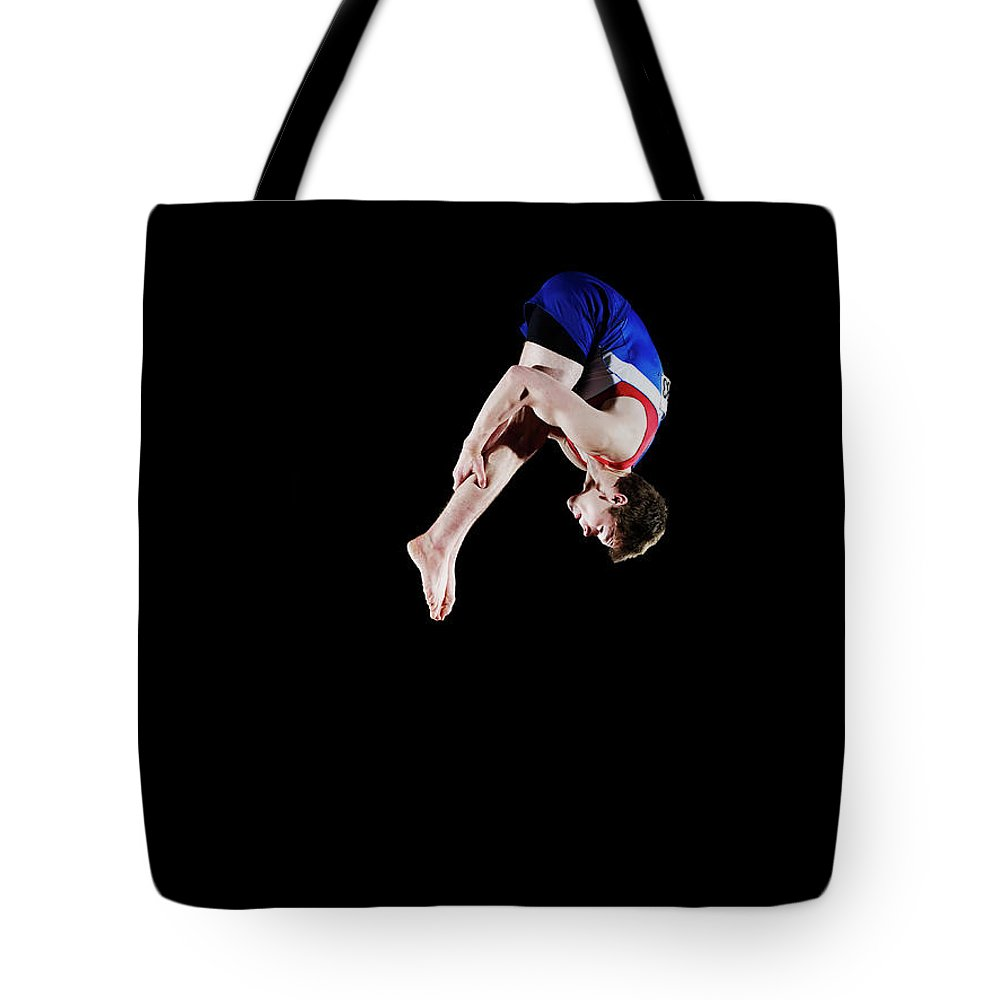 Focus Tote Bag featuring the photograph Male Gymnast 16-17 Mid Air, Black by Thomas Barwick