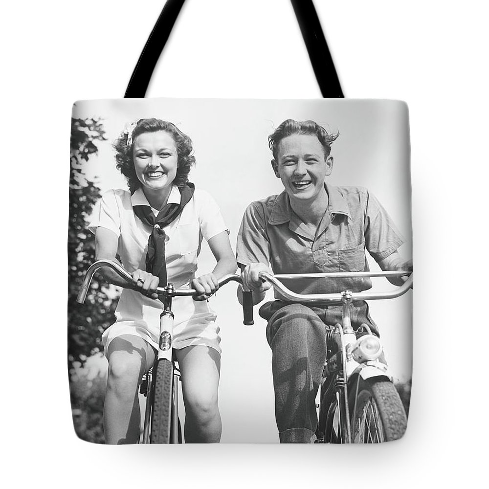 Young Men Tote Bag featuring the photograph Man And Woman Riding Bikes, B&w, Low by George Marks