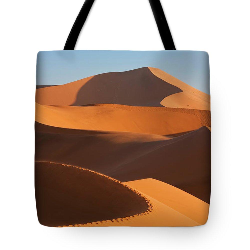 Shadow Tote Bag featuring the photograph Man Climbing Sand Dunes, Namib Desert by Peter Adams