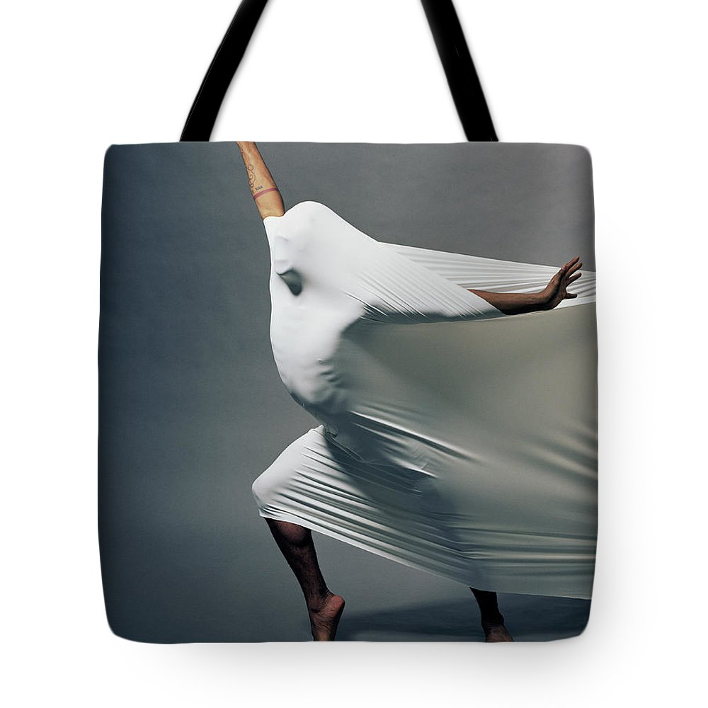 Hand Raised Tote Bag featuring the photograph Man Pressing Into Fabric, Arms Extended by Pm Images