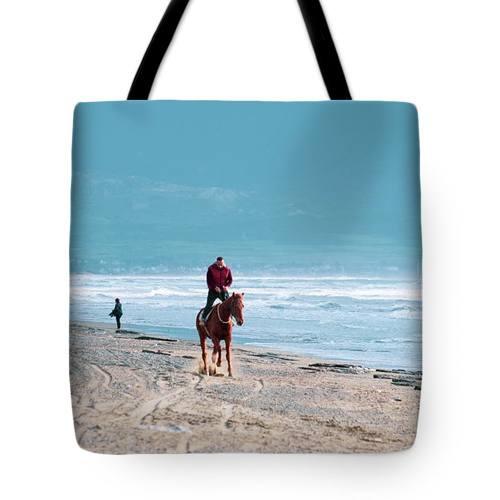 Akdeniz Tote Bag featuring the photograph Man Riding On A Brown Galloping Horse On Ayia Erini Beach In Cyp by Iordanis Pallikaras