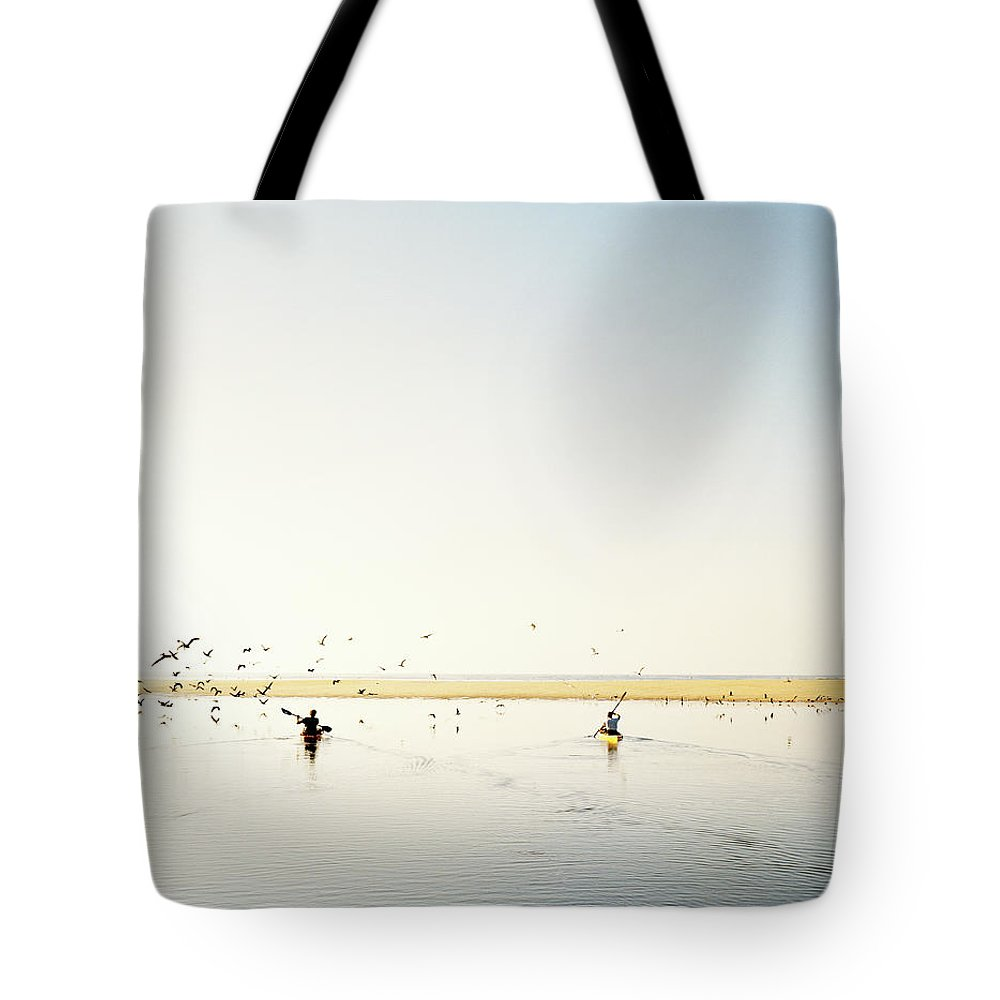 People Tote Bag featuring the photograph Men Paddling Kayaks To The Beach by Julien Capmeil