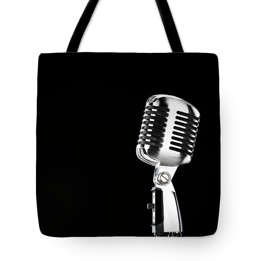 Music Tote Bag featuring the photograph Microphone Against Black Background by Peter Dazeley