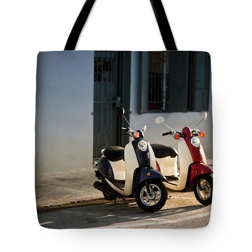 In A Row Tote Bag featuring the photograph Motorbikes Parked On The Road by Pgiam