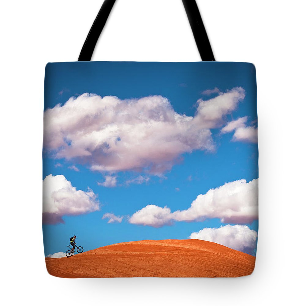 Slickrock Trail Tote Bag featuring the photograph Mountain Biker Climbing On Slick Rock by Visualcommunications