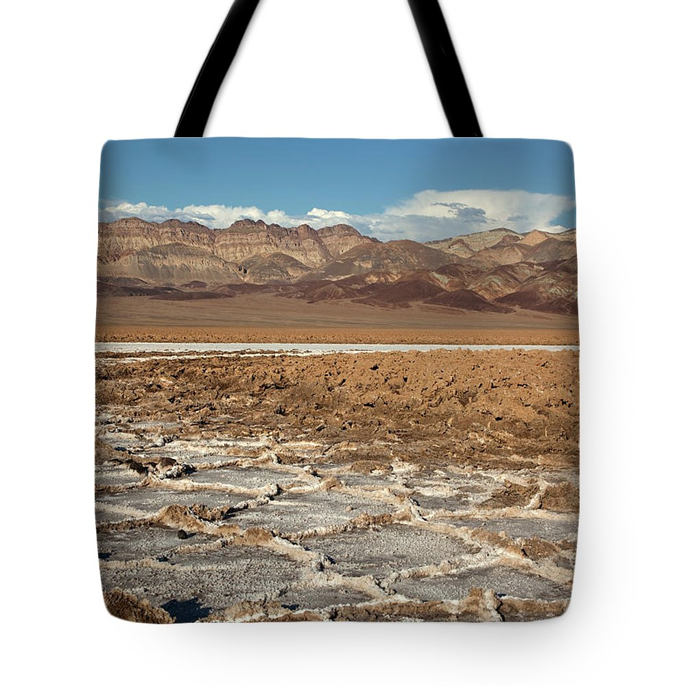 Badlands Tote Bag featuring the photograph Muddy Salt Flats And Black Mountains by Milehightraveler