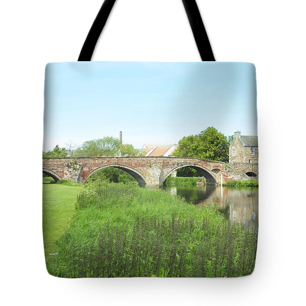 River Tote Bag featuring the photograph old bridge over river Tyne in Haddington by Victor Lord Denovan