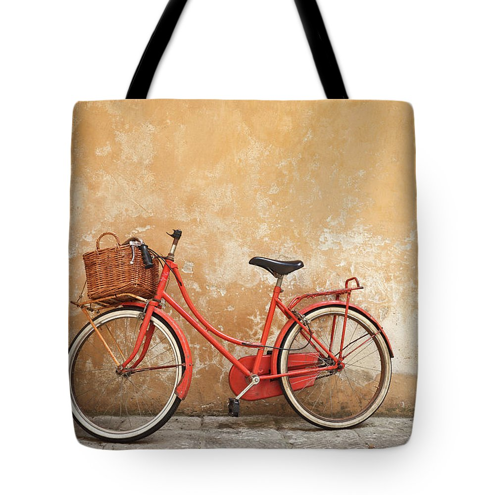 Leaning Tote Bag featuring the photograph Old Red Bike Against A Yellow Wall In by Romaoslo