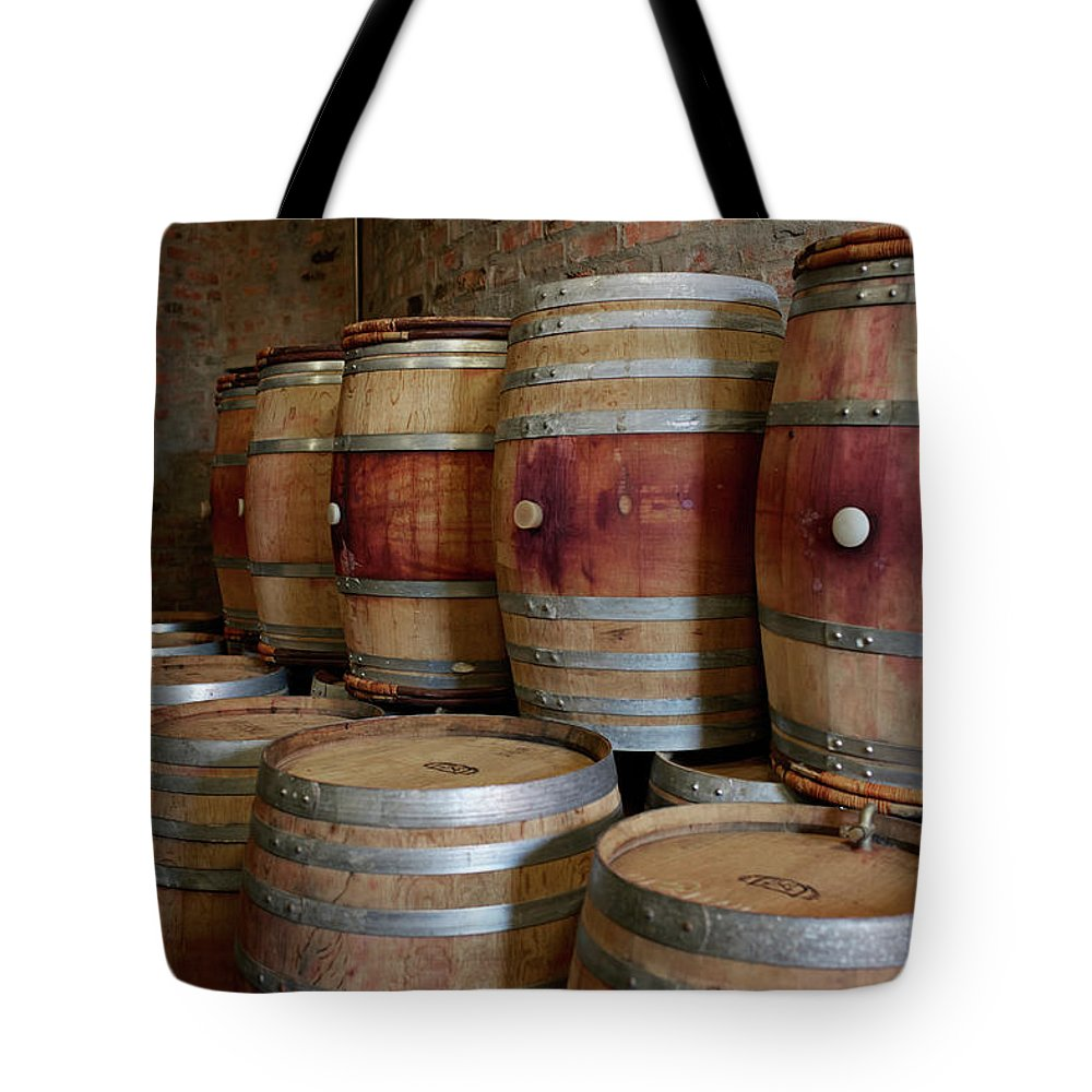 Stellenbosch Tote Bag featuring the photograph Pile Of Wooden Barrels At Winery by Klaus Vedfelt
