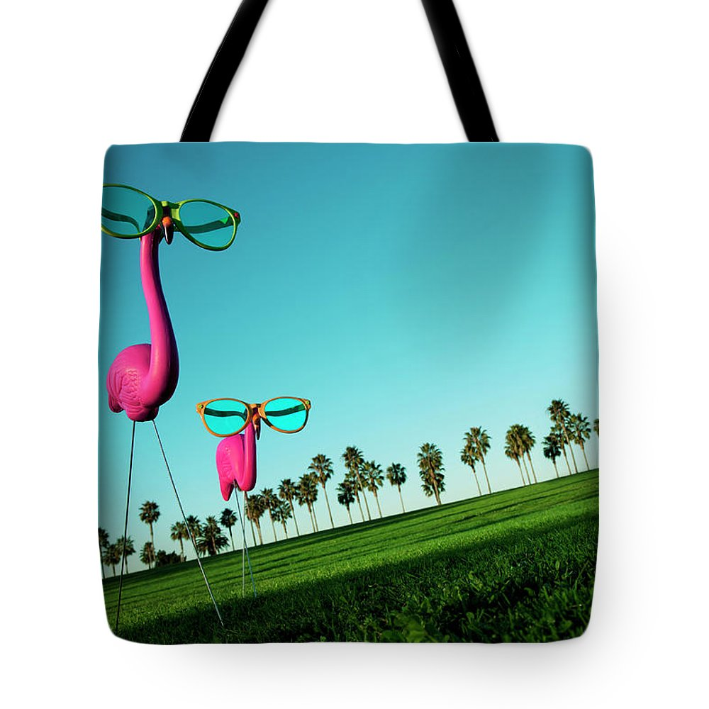 Artificial Tote Bag featuring the photograph Plastic Pink Flamingos On A Green Lawn by Skodonnell