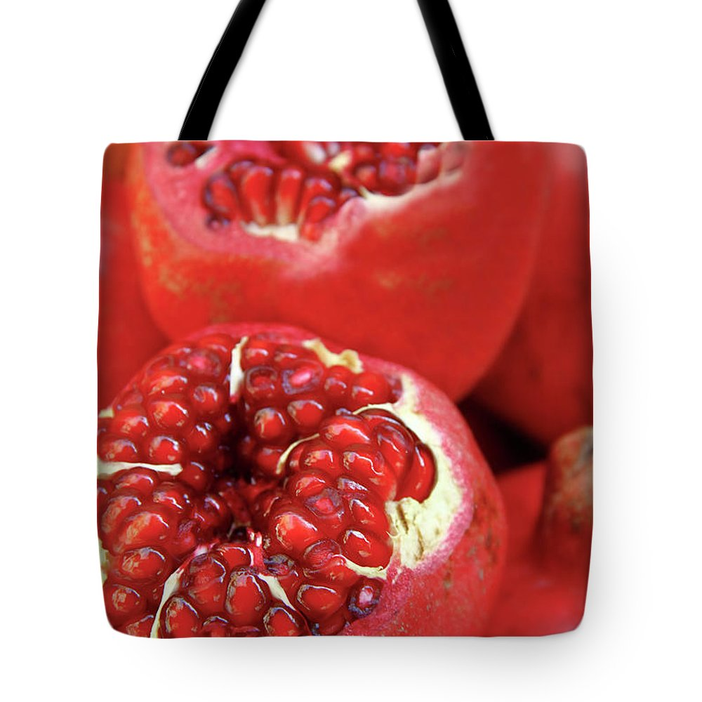 Fermenting Tote Bag featuring the photograph Pomegranates by Oonal