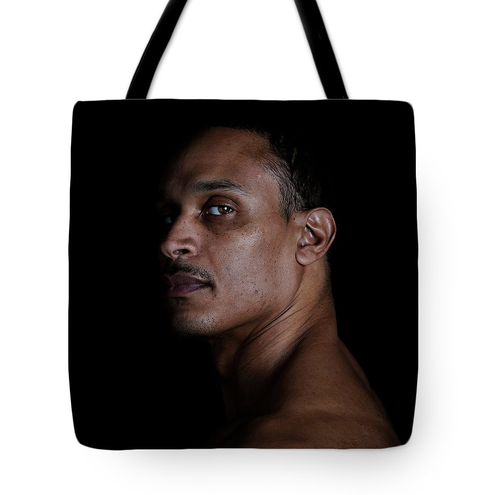 People Tote Bag featuring the photograph Portrait Of A Man On A Black Background by Michael Duva
