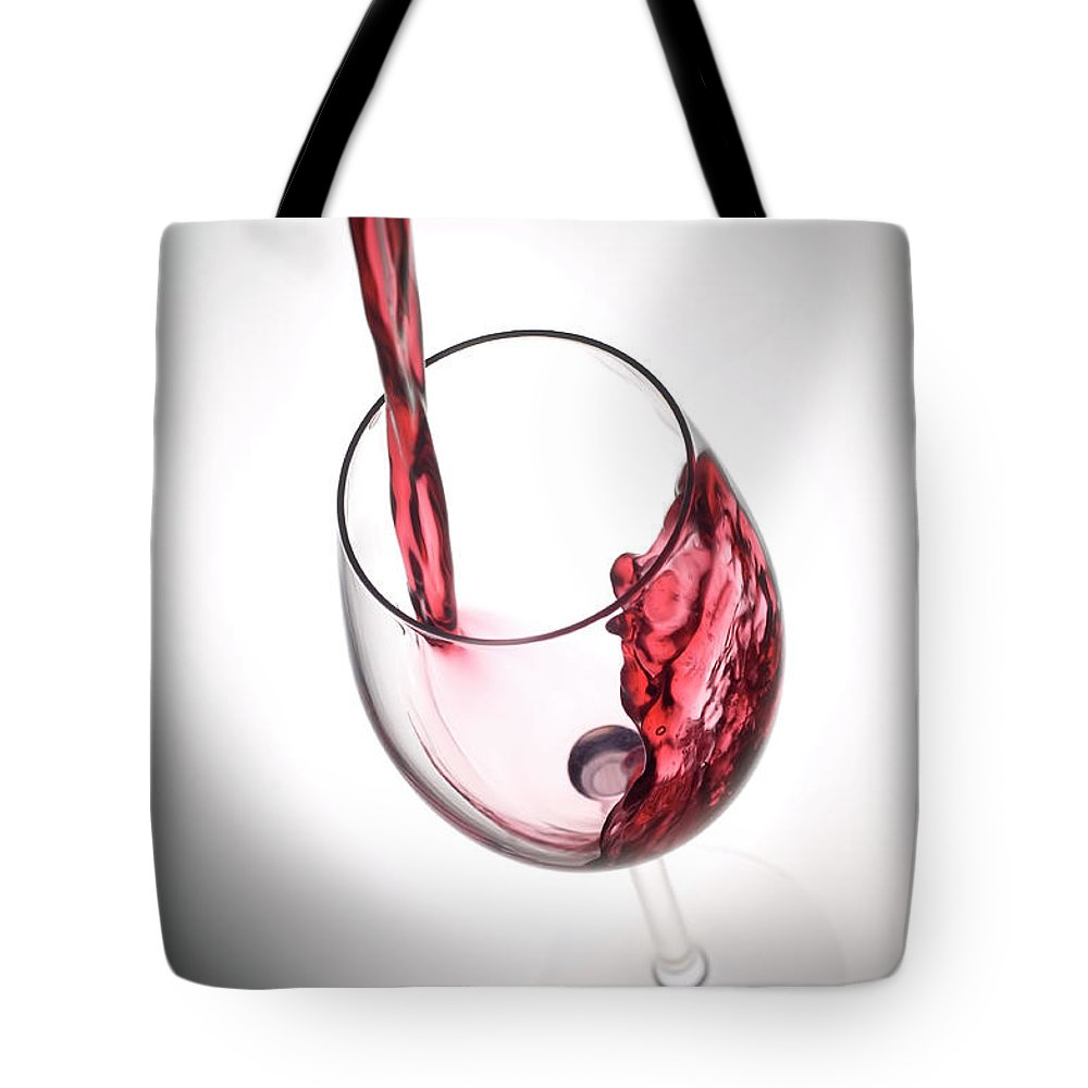 Alcohol Tote Bag featuring the photograph Pouring Red Wine Into A Glass by Stockcam