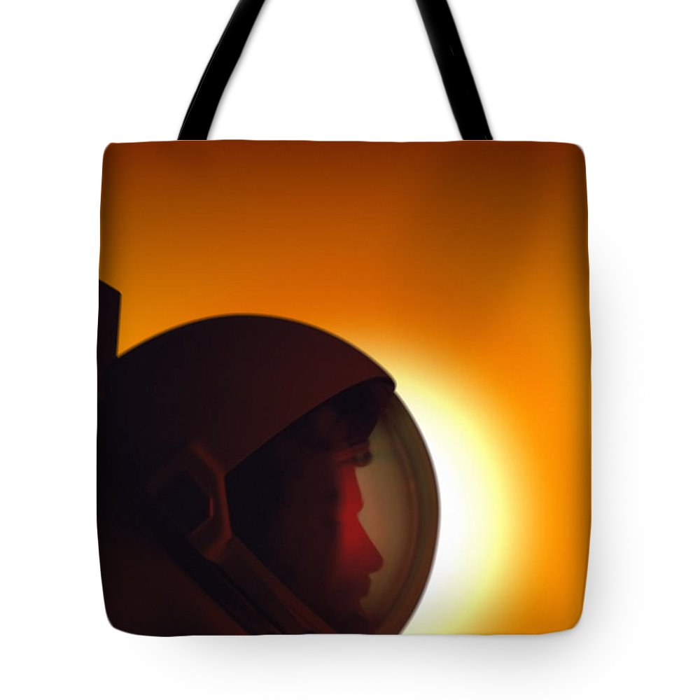 Orange Color Tote Bag featuring the photograph Profile Of A Helmeted Astronaut Against by Photodisc