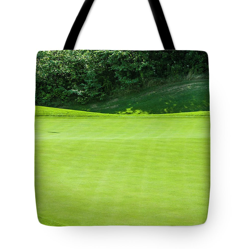 The End Tote Bag featuring the photograph Putting Green And Flag At A Golf Course by Stuart Dee