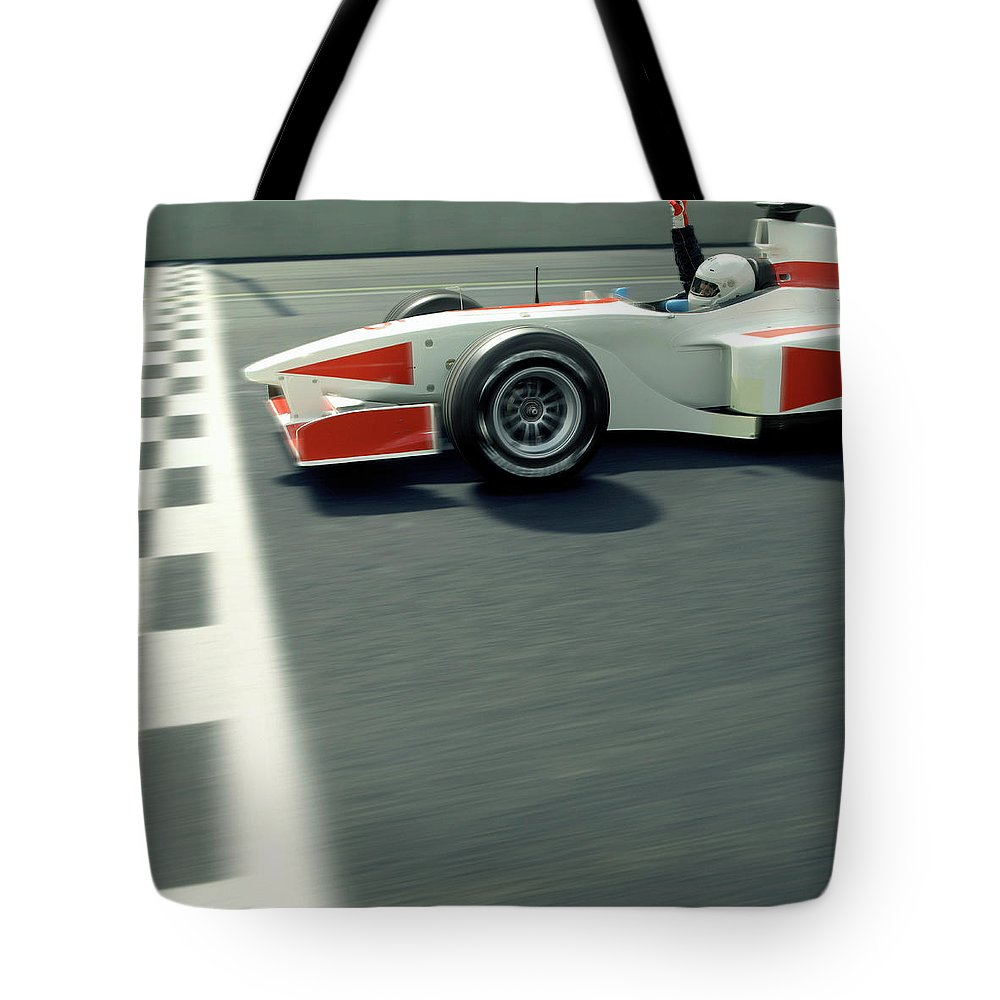 Aerodynamic Tote Bag featuring the photograph Racing Driver Crossing Finishing Line by Alan Thornton
