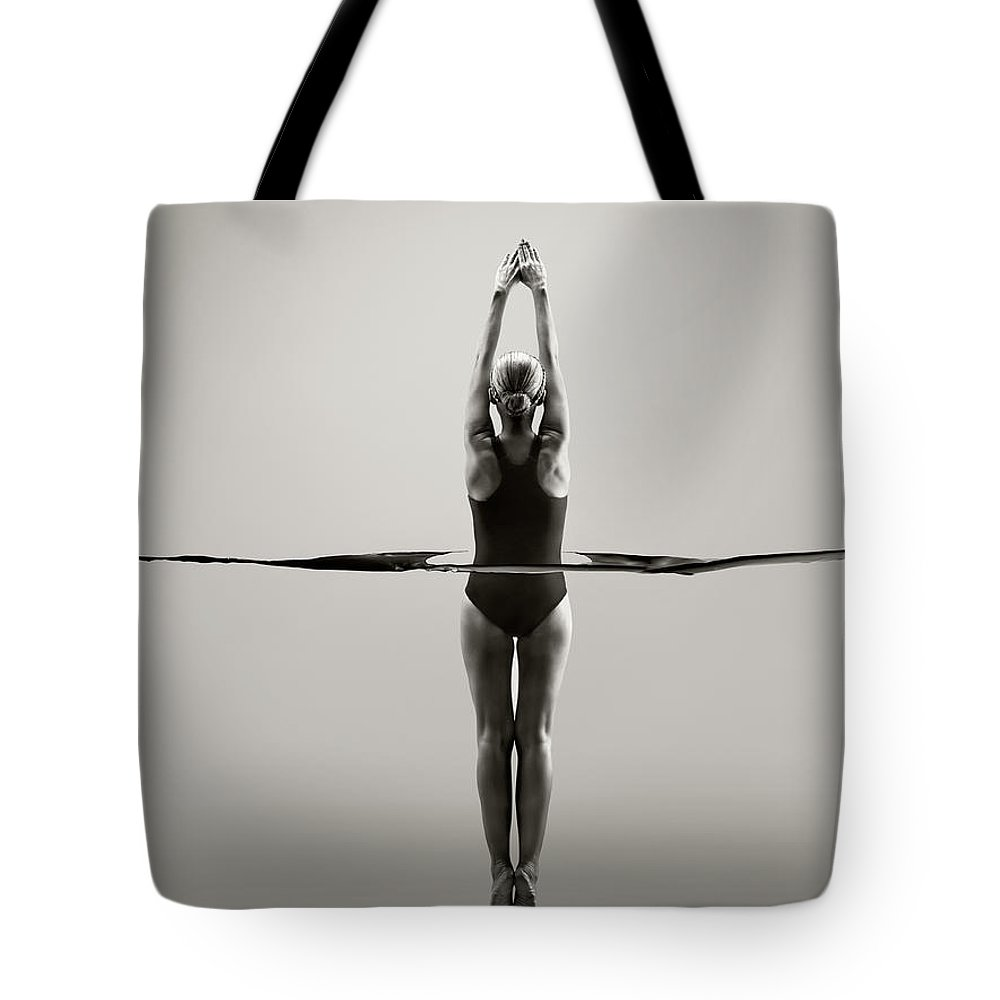 Diving Into Water Tote Bag featuring the photograph Rear View Of Female Swimmer by Jonathan Knowles
