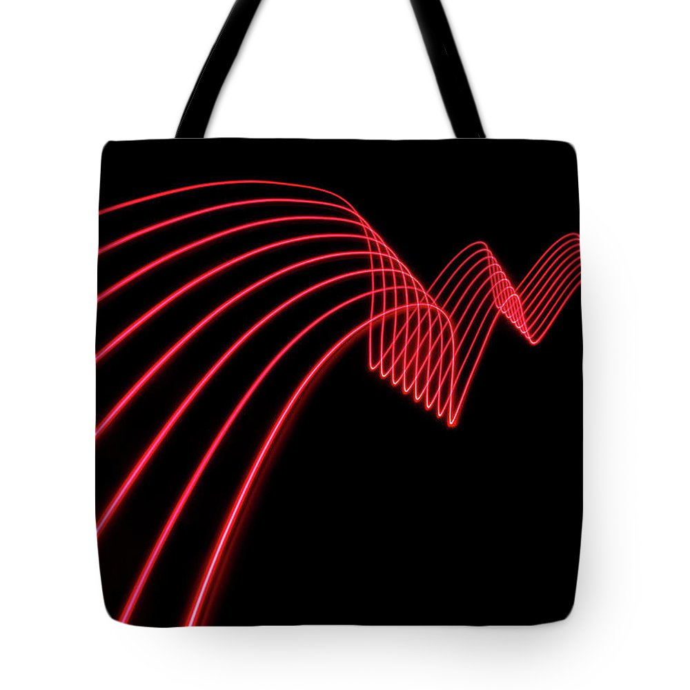 Laser Tote Bag featuring the photograph Red Abstract Coloured Lights Trails And by John Rensten