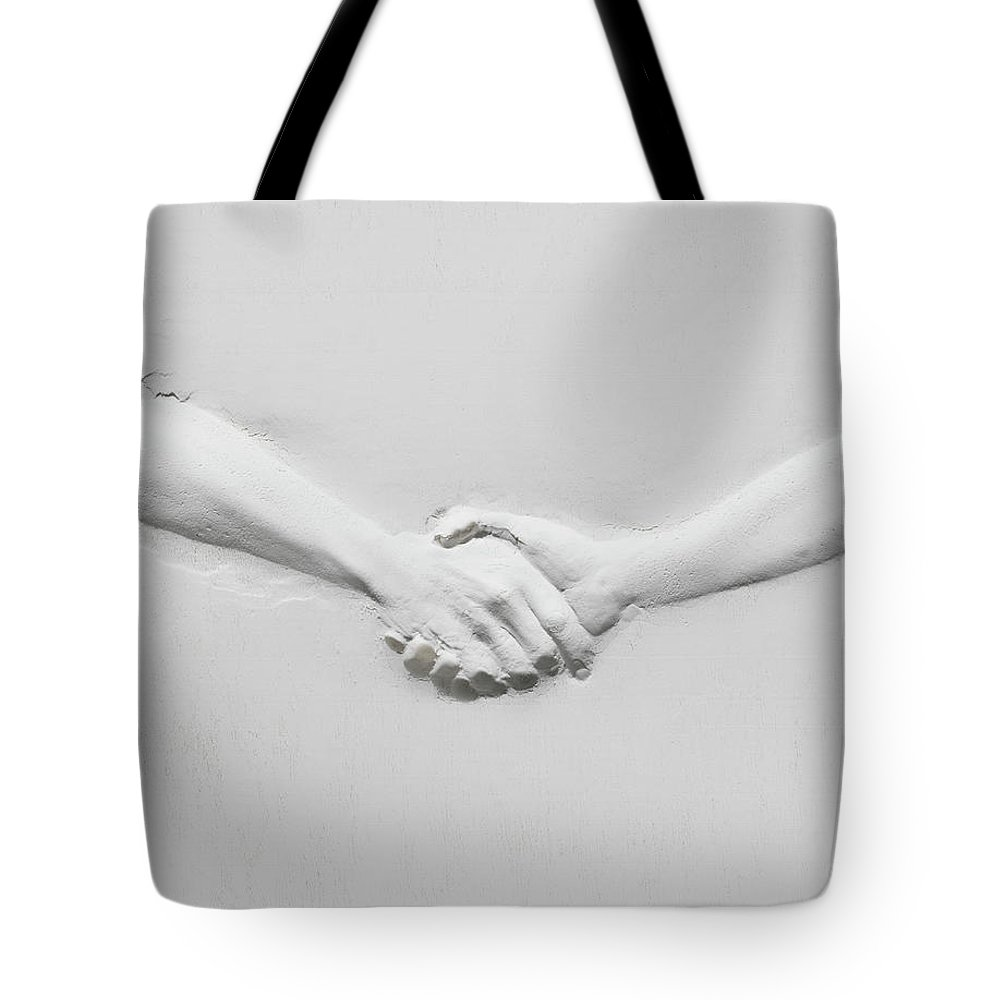 Human Arm Tote Bag featuring the photograph Relief Of Handshake by Henrik Sorensen