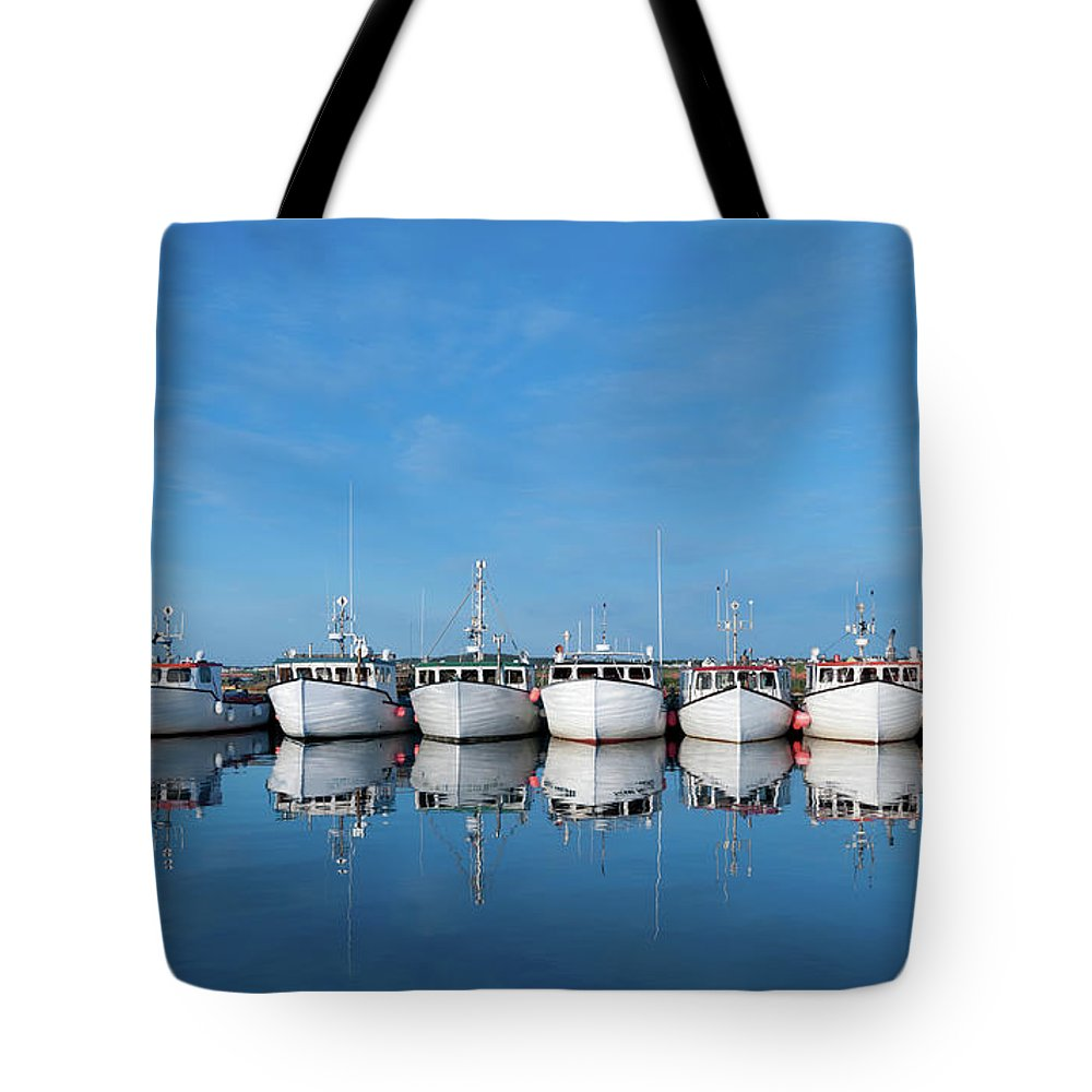 Iles De La Madeleine Tote Bag featuring the photograph Row Of Boats With Reflection by Pndtphoto