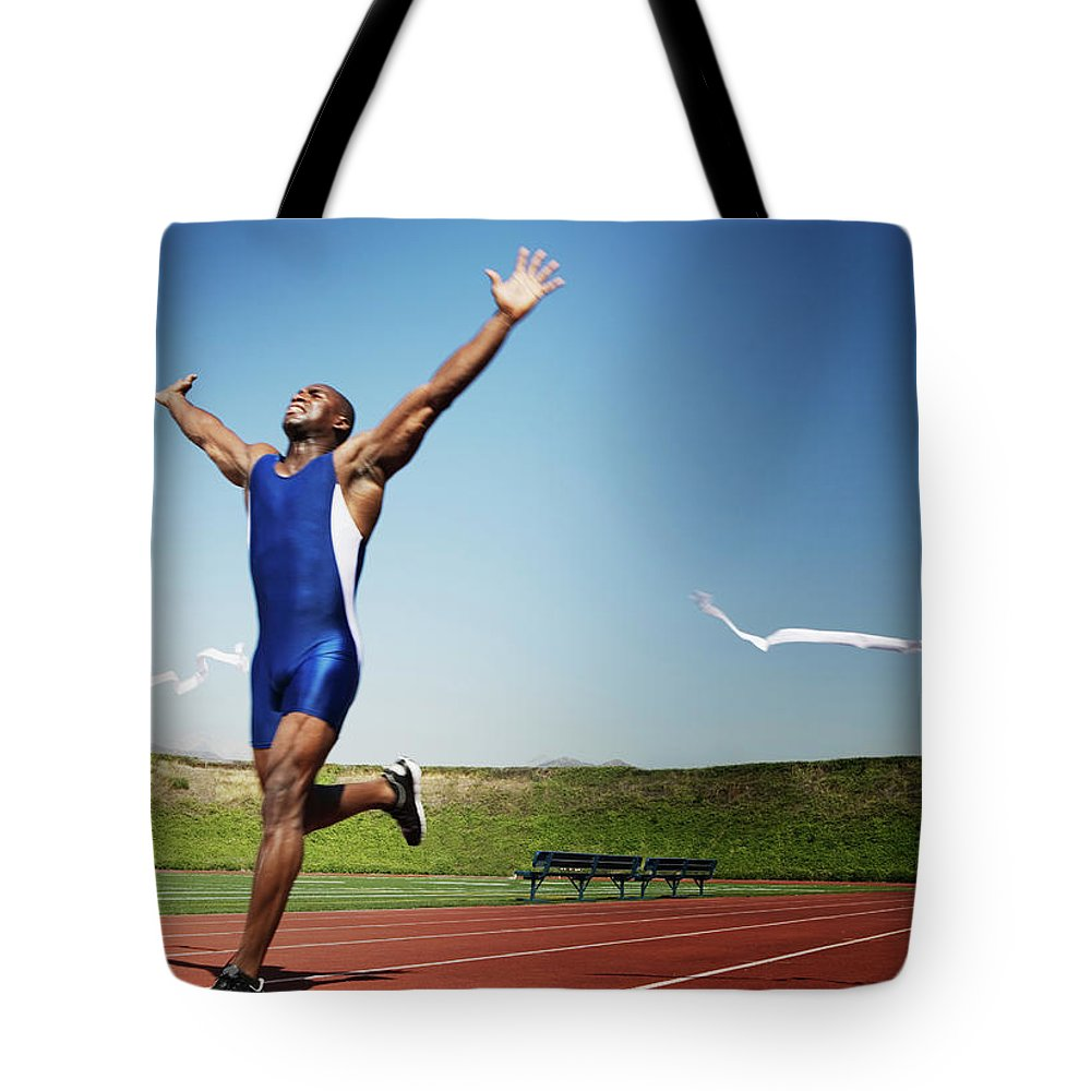 Human Arm Tote Bag featuring the photograph Runner Crossing Finish Line by Jupiterimages