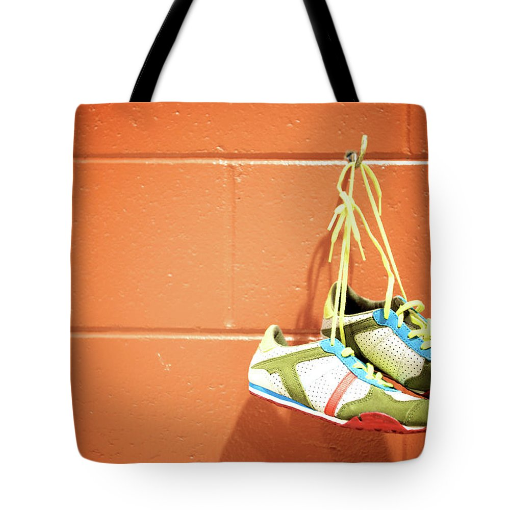 Hanging Tote Bag featuring the photograph Runnig Shoes Hanging On A Hook by Pascalgenest