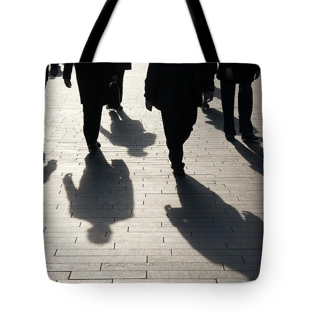 Shadow Tote Bag featuring the photograph Shadow Team Of Commuters Walking On by Peskymonkey