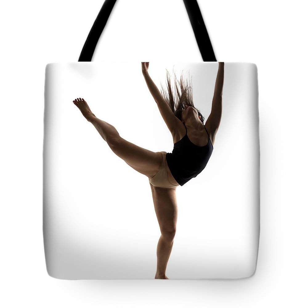 Ballet Dancer Tote Bag featuring the photograph Silhouette Of A Performing Dancer by Opla
