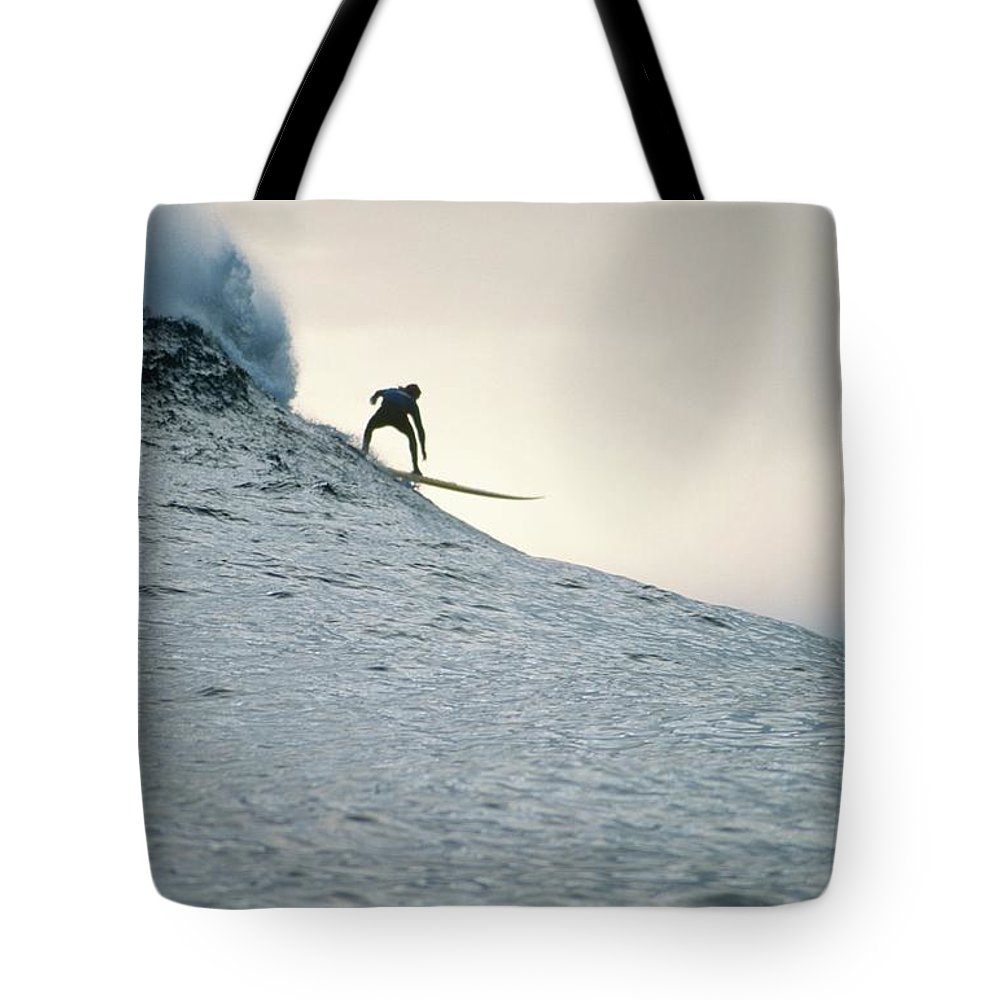 Scenics Tote Bag featuring the photograph Silhouette Of A Surfer Riding A Wave by Dominic Barnardt