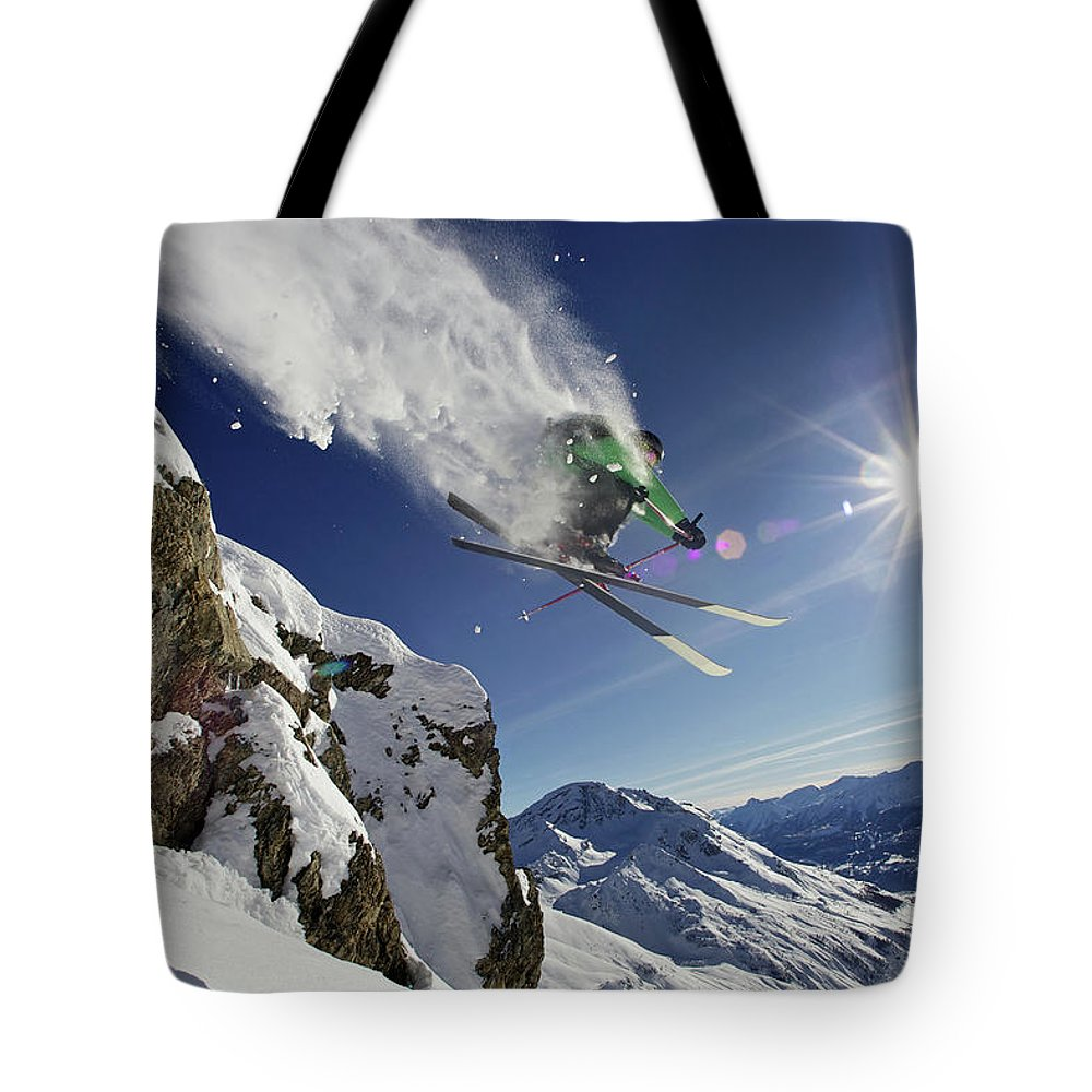 Young Men Tote Bag featuring the photograph Skier In Midair On Snowy Mountain by Michael Truelove