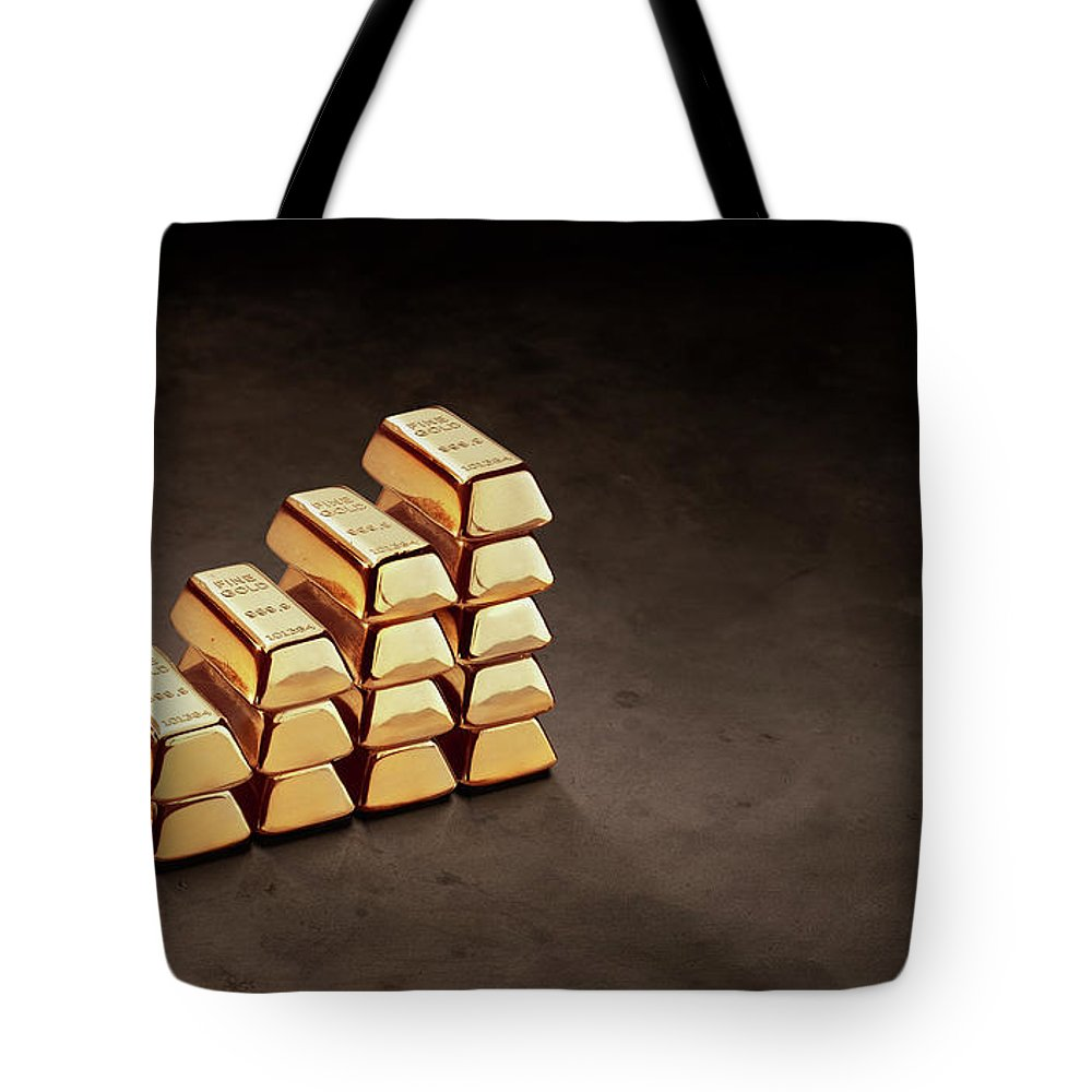 In A Row Tote Bag featuring the photograph Stepped Stack Of Gold On Dark Surface by Anthony Bradshaw