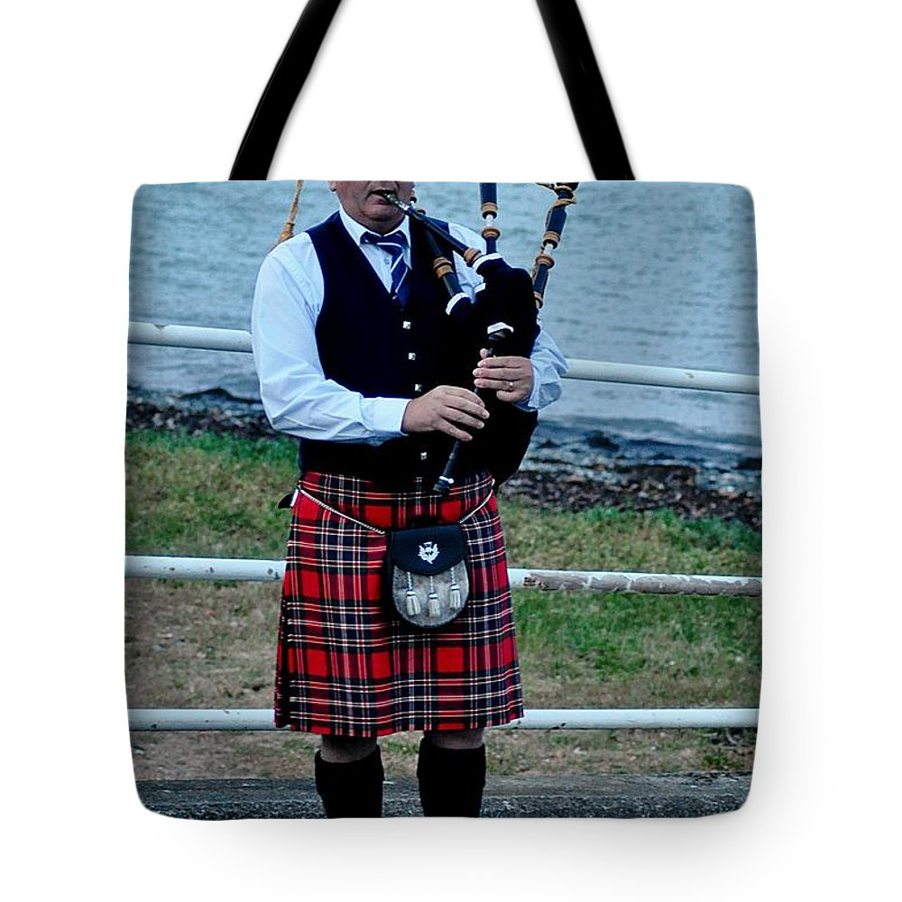 Highland Pipes Tote Bag featuring the photograph The Lone Piper by John Hughes