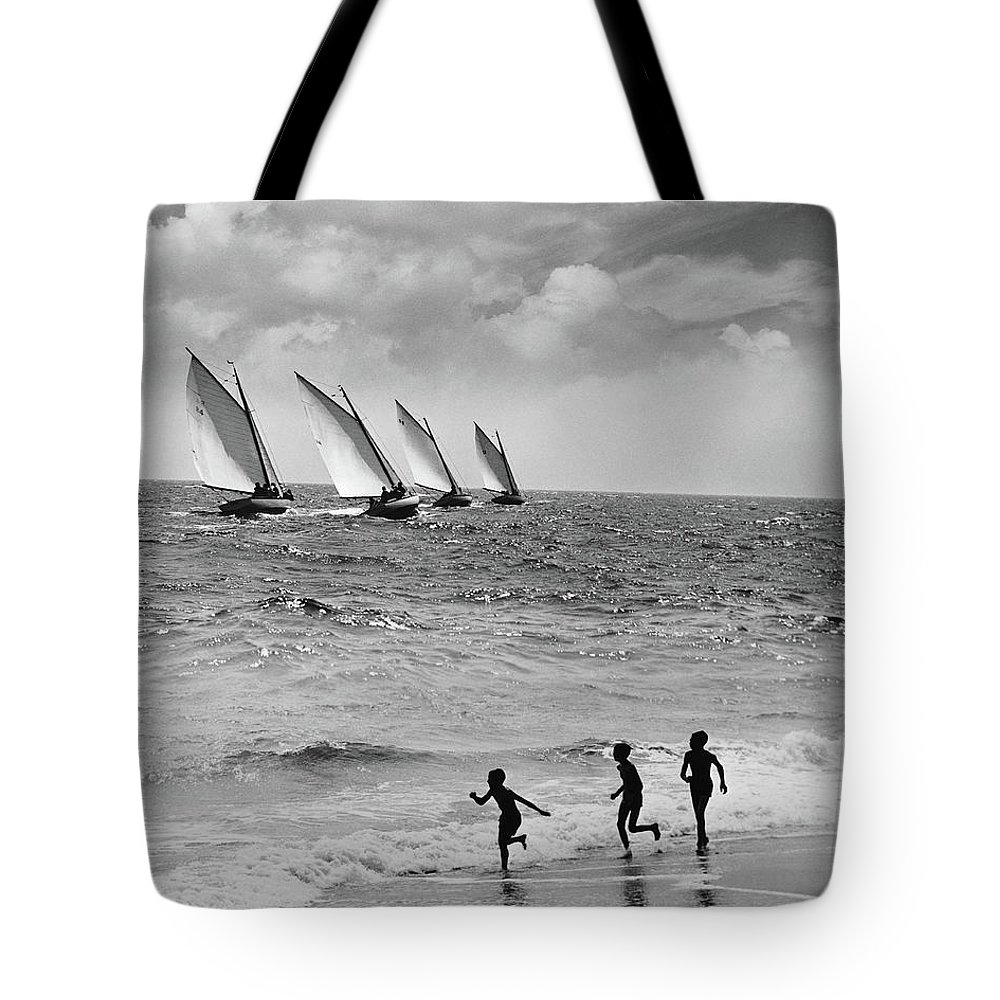 Following Tote Bag featuring the photograph Three Boys Running Along Beach by Stockbyte