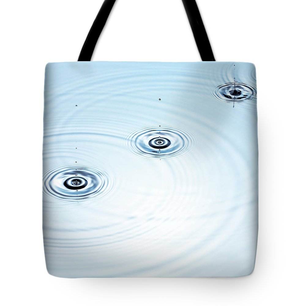 Purity Tote Bag featuring the photograph Three Drops Of Water Falling Into A by Pier